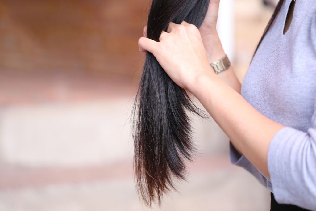 Woman holding at damaged splitting ends of hair, Haircare concep