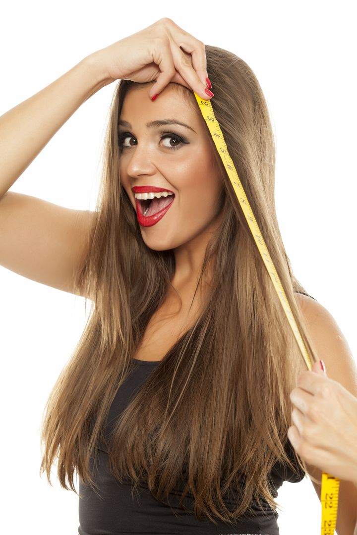 young happy beautiful woman measured her hair with a measuring tape